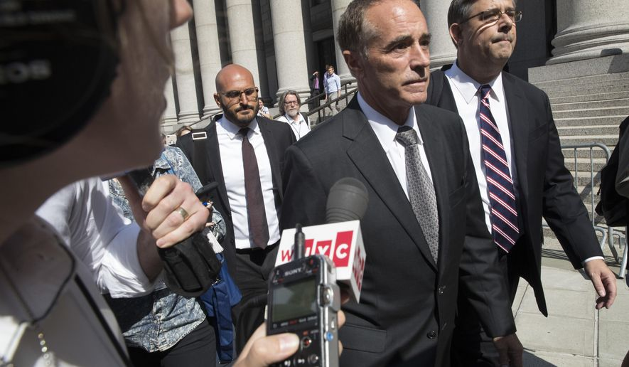 FILE - In this Wednesday, Aug. 8, 2018, file photo, Republican U.S. Rep. Christopher Collins, center, is surrounded by reporters as he leaves federal court, in New York. On Friday, Jan. 17, 2020, U.S. District Judge Vernon Broderick in Manhattan will sentence Collins for conspiring in an insider trading scheme. (AP Photo/Mary Altaffer, File)