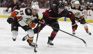Anaheim Ducks right wing Ondrej Kase (25), of the Czech Republic, and Carolina Hurricanes defenseman Haydn Fleury (4) chase the puck during the third period of an NHL hockey game in Raleigh, N.C., Friday, Jan. 17, 2020. Anaheim won 2-1 in overtime. (AP Photo/Gerry Broome)