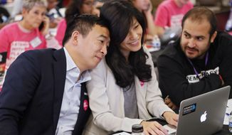FILE- In this Nov. 21, 2019, file photo, Democratic presidential candidate former technology executive Andrew Yang, leans on his wife with his wife Evelyn, as they join in at a Fair Fight phone bank at Ebenezer Baptist Church in Atlanta. The wife of Democratic presidential candidate Andrew Yang says she was sexually assaulted by her OB-GYN while she was pregnant with the couple's first child. (Bob Andres/Atlanta Journal-Constitution via AP)
