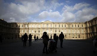 Tourists walk in the courtyard of the Louvre museum, in Paris, Friday, Dec. 13, 2019. Ongoing nationwide strikes have dented profits at Paris stores and restaurants, but tourists from around the world have continued to visit the City of Light as the holiday season approaches, according to the Paris tourism office. (AP Photo/Thibault Camus)