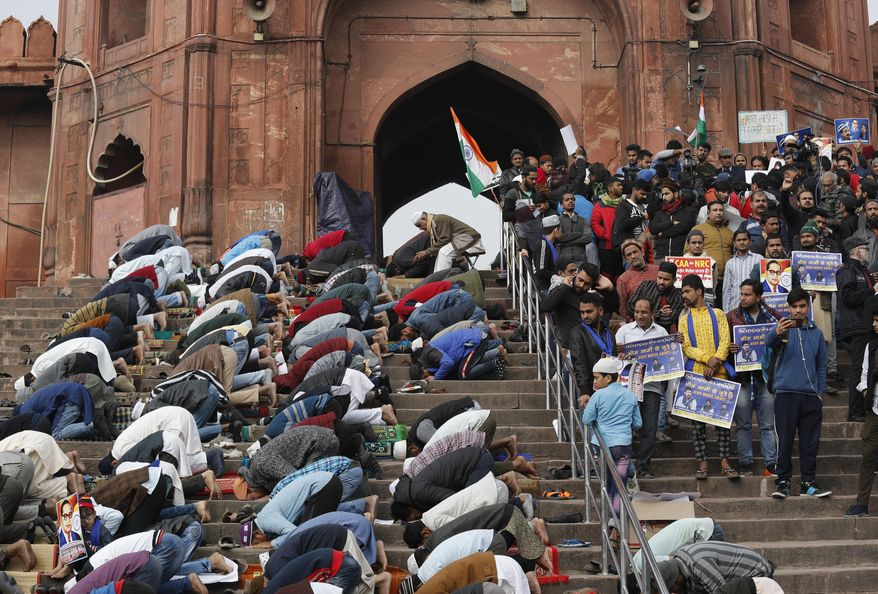 Indian Muslims offer prayers, as activists of Bhim Army wait for the start of a protest against a new Citizenship law, in New Delhi, India, Friday, Jan. 17, 2020. Protests against India's citizenship law that excludes Muslim immigrants continue in Indian cities in an unabating strong show of dissent against the Hindu nationalist government of Prime Minister Narendra Modi. The protest at a 17th century mosque, Jama Masjid, was led by Chandrashekhar Azad, leader of the Bhim Army, a political party of Dalits who represent Hinduism's lowest caste. (AP Photo/Manish Swarup)