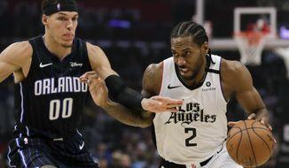 Los Angeles Clippers forward Kawhi Leonard, right, drives around Orlando Magic forward Aaron Gordon during the second half of an NBA basketball game in Los Angeles, Thursday, Jan. 16, 2020. The Clippers won 122-95. (AP Photo/Chris Carlson)