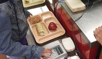 In this Thursday, May 4, 2017, file photo, a third-grader punches in her student identification to pay for a meal at Gonzales Community School in Santa Fe, N.M. The Trump administration is proposing a rollback of nutrition guidelines for federal school meals programs that had been promoted by Michelle Obama as part of her campaign to combat child obesity. (AP Photo/Morgan Lee, file)