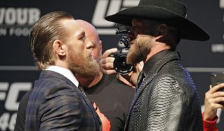 "Conor McGregor, left, and Donald ""Cowboy"" Cerrone pose for photographers during a news conference for a UFC 246 mixed martial arts bout, Wednesday, Jan. 15, 2020, in Las Vegas. The two are scheduled to fight in a welterweight bout Saturday. (AP Photo/John Locher)"