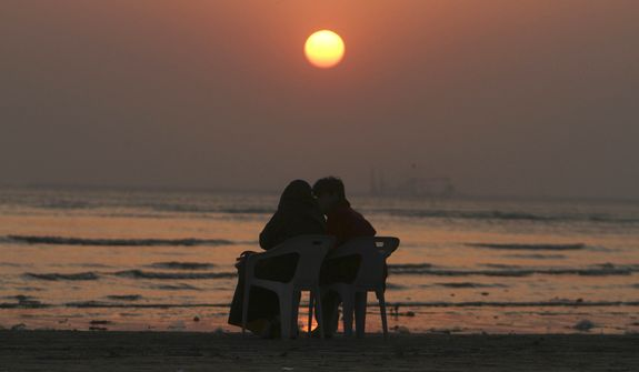 A couple shares a quiet moment at sunrise. (AP Photo/Fareed Khan)