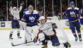 Washington Capitals' Alex Ovechkin celebrates after scoring a goal during the third period of an NHL hockey game as New York Islanders goaltender Semyon Varlamov (40) watches Saturday, Jan. 18, 2020, in Uniondale, N.Y. Ovechkin scored three goals as the Capitals won 6-4. (AP Photo/Frank Franklin II)
