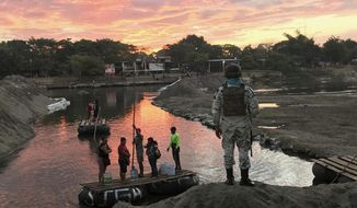 A Mexican National Guard looks at local residents crossing the Suchiate River, near Ciudad Hidalgo, on the Mexican border with Guatemala, Friday, Jan. 17, 2020. Border security forces in southern Mexico were preparing Friday for the expected arrival of hundreds of Central Americans traveling through Guatemala in hopes to reach United States. (AP Photo/Maria Verza)