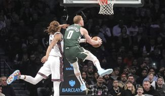 Milwaukee Bucks guard Donte DiVincenzo (0) drives past Brooklyn Nets forward Caris LeVert (22), during a NBA basketball game, Saturday Jan. 18, 2020 in New York. (AP Photo/Bebeto Matthews)