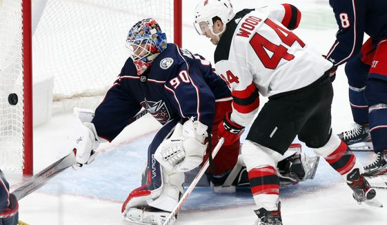 Columbus Blue Jackets goalie Elvis Merzlikins, left, of Latvia, stops a shot in front of New Jersey Devils forward Miles Wood during the third period an NHL hockey game in Columbus, Ohio, Saturday, Jan. 18, 2020. (AP Photo/Paul Vernon)