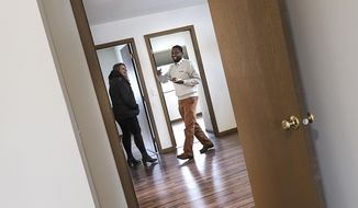 Ahmed Abdi smiles while showing visitors around his future home during a Central Minnesota Habitat for Humanity dedication Wednesday, Jan. 8, 2020, in St. Cloud, Minn. The home is the 100th built by the organization over the past 30 years. (Dave Schwarz/The St. Cloud Times via AP)