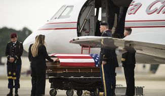 Tarah McLaughlin, the widow of Staff Sgt. Ian Paul McLaughlin, touches her husband's coffin on Saturday, Jan. 18, 2020, on Fort Bragg, N.C. McLaughlin was killed Jan. 11 in Afghanistan. (Andrew Craft /The Fayetteville Observer via AP)