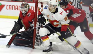 Calgary Flames left wing Andrew Mangiapane (88) attempts a wraparound as Ottawa Senators goaltender Marcus Hogberg (35) covers the near post during first-period NHL hockey game action in Ottawa, Ontario, Saturday, Jan. 18, 2020. (Fred Chartrand/The Canadian Press via AP)