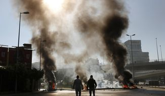 Two men walk near burning tires set on fire by anti-government protesters during ongoing protests after weeks of calm in Beirut, Lebanon, Tuesday, Jan. 14, 2020. Protesters blocked several roads around the capital and in other areas on Tuesday in renewed rallies, after a brief hiatus, against the ruling elite who have failed to address the economy's downward spiral. (AP Photo/Hussein Malla)