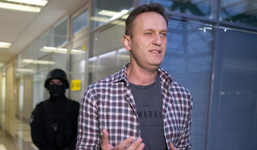 Russian opposition leader Alexei Navalny speaks to the media as policemen stand guard at the Foundation for Fighting Corruption office in Moscow, Russia. (AP Photo/Alexander Zemlianichenko, File)