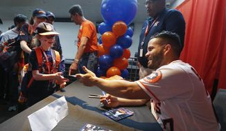 Jose Altuve signs autographs for young fans during the baseball team's FanFest at Minute Maid Park on Saturday, Jan. 18, 2020, in Houston. (Steve Gonzales/Houston Chronicle via AP) **FILE**