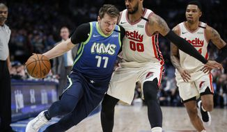 Dallas Mavericks forward Luka Doncic (77) drives as Portland Trail Blazers forward Carmelo Anthony (00) defends during the first half of an NBA basketball game Friday, Jan. 17, 2020, in Dallas. (AP Photo/Brandon Wade)