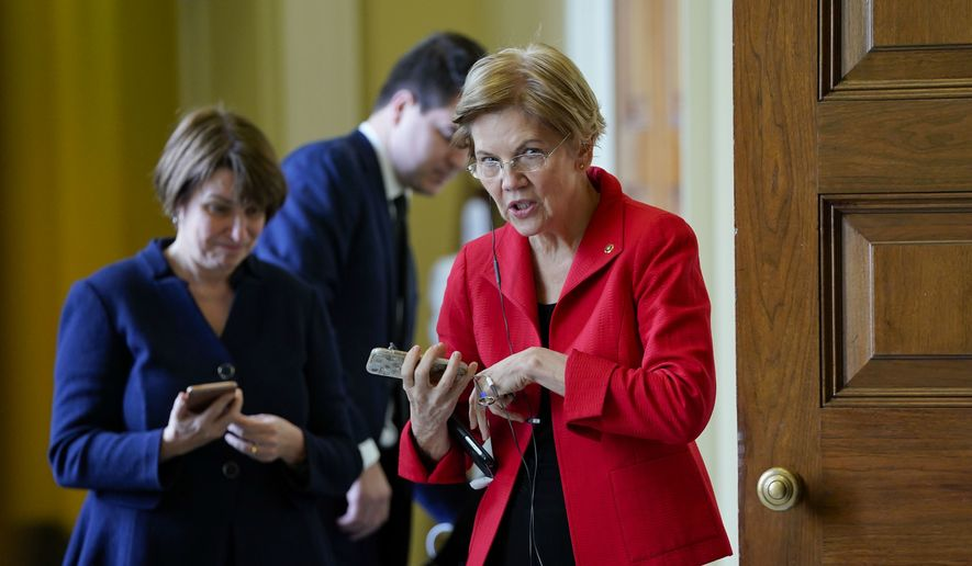 In this Nov. 14, 2018, photo, Sen. Amy Klobuchar, D-Minn., left, and Sen. Elizabeth Warren, D-Mass., right, talk on their phones before heading into meetings with fellow Democrats on Capitol Hill in Washington. Their campaigns are not yet official, but some Democrats are beginning to frame the 2020 fight on their terms. Warren has taken aggressive stances that suggest a willingness to take on President Donald Trump directly.  (AP Photo/Pablo Martinez Monsivais)
