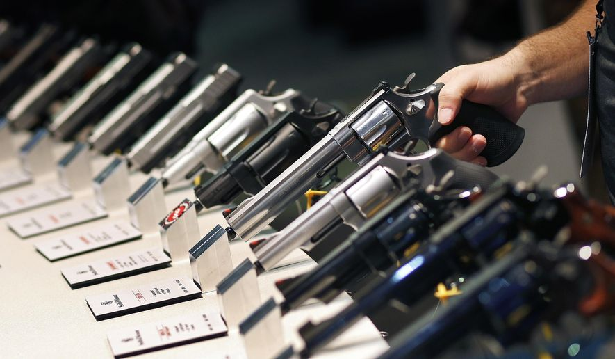 In this Jan. 19, 2016, file photo, handguns are displayed at the Smith & Wesson booth at the Shooting, Hunting and Outdoor Trade Show in Las Vegas. (AP Photo/John Locher, File)