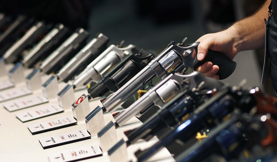 In this Jan. 19, 2016, file photo, handguns are displayed at the Smith & Wesson booth at the Shooting, Hunting and Outdoor Trade Show in Las Vegas. (AP Photo/John Locher, File)  **FILE**