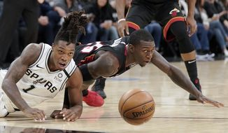 San Antonio Spurs' Lonnie Walker IV (1) and Miami Heat's Kendrick Nunn fall as they chase the ball during the first half of an NBA basketball game, Sunday, Jan. 19, 2020, in San Antonio. (AP Photo/Darren Abate)