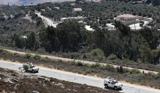 FILE - Sept. 2, 2019, file photo, Spanish UN peacekeepers patrol along the Lebanese-Israeli border, with the Israeli village of Metulla, background, in the village of Kfar Kila, Lebanon. Israel's military said it began construction of an underground defense system Sunday along its northern frontier with Lebanon to protect against cross-border tunnels. (AP Photo/Hussein Malla, File)