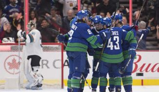Vancouver Canucks defenseman Quinn Hughes (43) celebrates his goal past San Jose Sharks goaltender Aaron Dell (30) with his teammates during the third period of an NHL hockey game in Vancouver, British Columbia, Saturday, Jan. 18, 2020. (Jonathan Hayward/The Canadian Press via AP)