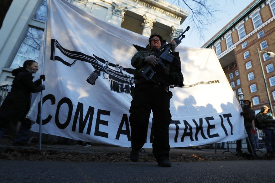 Demonstrators stand outside a security zone before a pro gun rally, Monday, Jan. 20, 2020, in Richmond, Va. Thousands of pro-gun supporters are expected at the rally to oppose gun control legislation like universal background checks that are being pushed by the newly elected Democratic legislature. (AP Photo/Julio Cortez)