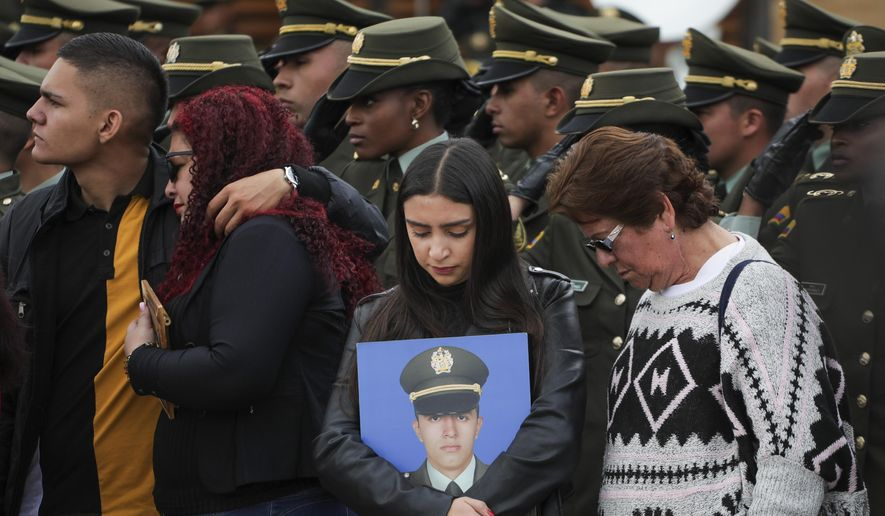 In this file photo, relatives attend a ceremony marking one year since a car bomb attack on the police academy in Bogota, Colombia, Monday, Jan. 20, 2020. Colombian government officials blamed rebels of the National Liberation Army, ELN, for the bombing that killed at least 21 people on Jan. 17, 2019. (AP Photo/Ivan Valencia) **FILE**