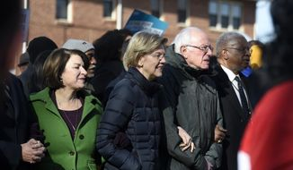 Democratic presidential rivals Amy Klobuchar, Elizabeth Warren and Bernie Sanders link arms during a Martin Luther King Jr. Day march on Monday, Jan. 20, 2020, in Columbia, S.C. (AP Photo/Meg Kinnard) **FILE**