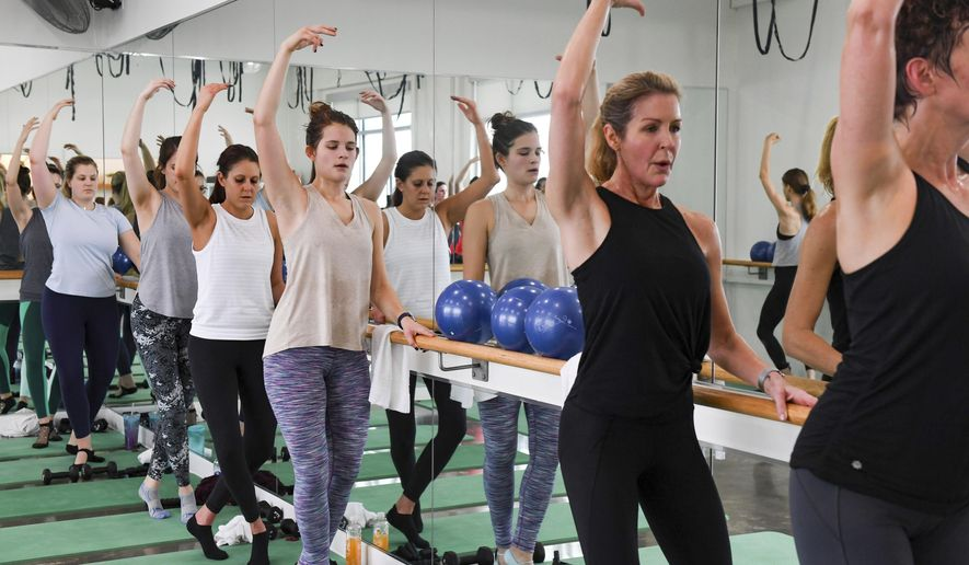 Women stand in fourth position at the barre during class on Monday, Dec. 30, at Define in Sioux Falls. (Erin Bormett /The Argus Leader via AP)/The Argus Leader via AP