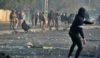 An anti-government protester throws a stone towards security forces during an ongoing protest in central Baghdad, Iraq, Monday, Jan. 20, 2020. (AP Photo/Hadi Mizban)