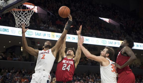 Virginia guard Braxton Key (2) and North Carolina State guard Devon Daniels (24) battle for rebound as Virginia center Jay Huff(30) and North Carolina State forward D.J. Funferfunk join in during the first half of an NCAA college basketball game in Charlottesville, Va., Monday, Jan. 20, 2020. (AP Photo/Lee Luther Jr.)
