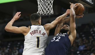 Minnesota Timberwolves' Karl-Anthony Towns is fouled by Denver Nuggets' Michael Porter Jr. in the first half of an NBA basketball game Monday, Jan. 20, 2020, in Minneapolis. (AP Photo/Stacy Bengs)