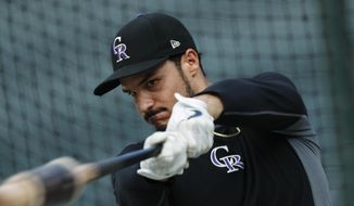 In this Sept. 27, 2019, file photo, Colorado Rockies third baseman Nolan Arenado warms up before a baseball game against the Milwaukee Brewers in Denver. Rockies star Arenado said he feels disrespected after Colorado general manager Jeff Bridich acknowledged listening to trade offers for the seven-time Gold Glove winner. Bridich told The Denver Post on Monday, Jan. 20, 2020, that he expected Arenado to be Colorado's third baseman this season after discussing potential deals involving the 28-year-old this winter. The five-time All-Star agreed to a $260 million, eight-year contract with the Rockies last February. (AP Photo/David Zalubowski, File) **FILE**