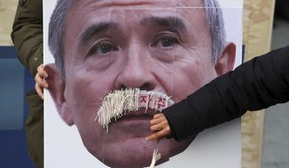 In this Dec. 13, 2019, photo, a protester plucks face mustache from a picture of U.S. Ambassador to South Korea Harry Harris during a rally to denounce the United States' policies against North Korea near the U.S. Embassy in Seoul, South Korea. Harris has some unusual explanations for the harsh criticism he's faced in his host country. His mustache, maybe? Or a Japanese ancestry that raises unpleasant reminders of Japan's former colonial domination of Korea? (Lee Yong-hwan/Newsis via AP) ** FILE **