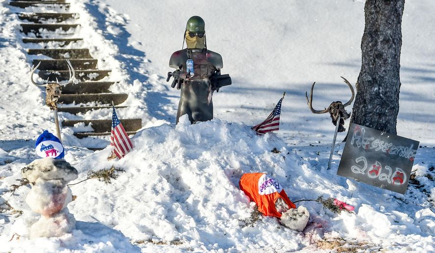 A snow display in the yard of Donald Hesseltine is seen Monday, Jan. 20, 2020, in Davenport, Iowa. Leaders in the city condemned Hesseltine's display, depicting a figure gunning down a snowman wearing a Bernie Sanders shirt and another adorned with a Democratic Party hat. (Meg McLaughlin/Quad City Times via AP)