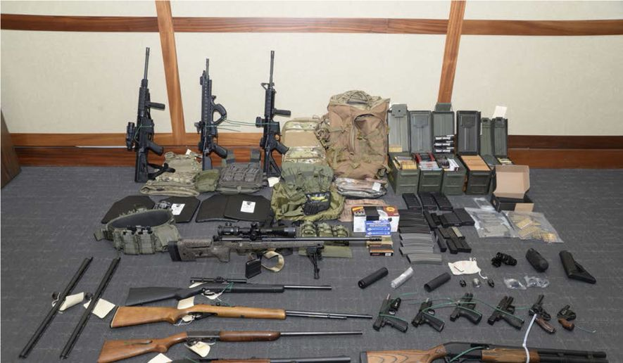 This file image provided by the Maryland U.S. District Attorney's Office shows a photo of firearms and ammunition that belonged to Christopher Paul Hasson, a Coast Guard lieutenant. Federal prosecutors recommend a 25-year prison sentence for Hasson, accused of stockpiling weapons and targeting Supreme Court justices, prominent Democrats and TV journalists. But defense attorneys dispute the government's claim that he is a domestic terrorist. (Maryland U.S. District Attorney's Office via AP, File)