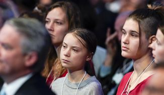 Swedish environmental activist Greta Thunberg, center, attends the speech of US President Donald Trump during a plenary session of the World Economic Forum in Davos, Switzerland, Tuesday, Jan. 21, 2020. The 50th annual meeting of the forum will take place in Davos from Jan. 21 until Jan. 24, 2020. (Gian Ehrenzeller/Keystone via AP)