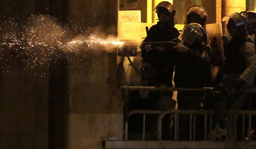 Riot police fire rubber bullets against anti-government protesters, during ongoing protests against the political elites who have ruled the country for decades, in Beirut, Lebanon, Sunday, Jan. 19, 2020. Lebanese security forces used tear gas, water cannons and rubber bullets in clashes with hundreds of anti-government protesters outside the country's Parliament on Sunday, as violence continued to escalate in a week of rioting in the capital. (AP Photo/Hassan Ammar)