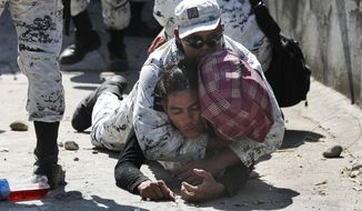 A Mexican National Guard detains a Central American migrant after he crossed the Suchiate River with a group of migrants from Guatemala into Mexico near Ciudad Hidalgo, Mexico, Monday, Jan. 20, 2020. More than a thousand Central American migrants hoping to reach United States marooned in Guatemala are walking en masse across a river leading to Mexico in an attempt to convince authorities there to allow them passage through the country. (AP Photo/Marco Ugarte)