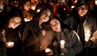 Caprice Cortez, Faith Goodsell, Autumn Barton and Mykaylla Darrow, all teammates on the Grantsville High School girls soccer team that Alexis Haynie played on, stand together at a candlelight vigil for the Haynie family at City Park in Grantsville, Utah, Monday, Jan. 20, 2020. Police say four members of the Haynie family were killed and one injured after being shot by a teenage family member on Jan. 17. (Spenser Heaps/The Deseret News via AP)