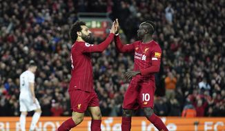 Liverpool's Mohamed Salah, front left, celebrates with Liverpool's Sadio Mane after scoring his side's opening goal during the English Premier League soccer match between Liverpool and Sheffield United at Anfield Stadium, Liverpool, England, Thursday, Jan. 2, 2020. (AP Photo/Jon Super)