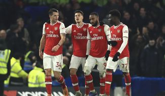 Arsenal's players celebrate a goal against Chelsea during the English Premier League soccer match between Chelsea and Arsenal at Stamford Bridge stadium in London England, Tuesday, Jan. 21, 2020. (AP Photo/Leila Coker)