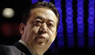 In this July 4, 2017, file photo, Interpol President Meng Hongwei delivers his opening address at the Interpol World Congress, in Singapore. China has sentenced the former president of Interpol Meng Hongwei to 13 years and six months in prison on charges of accepting bribes. (AP Photo/Wong Maye-E, File)