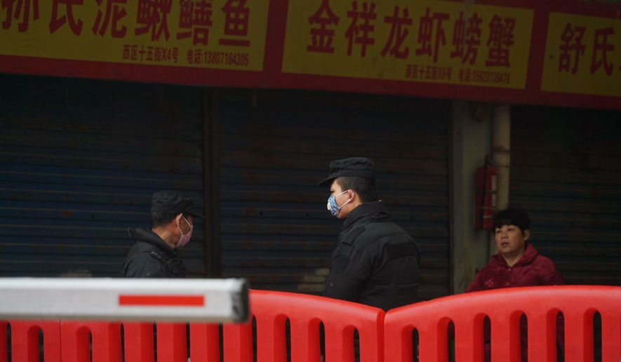Police stand guard outside Wuhan Huanan Wholesale Seafood Market, where a number of people related to the market fell ill with a virus in Wuhan, China, Tuesday, Jan. 21, 2020. Heightened precautions were being taken in China and elsewhere Tuesday as governments strove to control the outbreak of the coronavirus, which threatens to grow during the Lunar New Year travel rush. (AP Photo/Dake Kang)