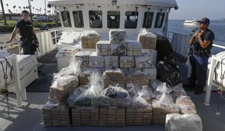 In this Aug. 29, 2019, file photo, members of the Coast Guard stand near seized cocaine in Los Angeles. (AP Photo/Chris Carlson, file)