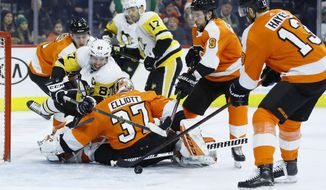 Pittsburgh Penguins' Sidney Crosby (87) tries to get a shot past Philadelphia Flyers' Brian Elliott (37) as Philippe Myers (5), Ivan Provorov (9) and Kevin Hayes (13) defend during the third period of an NHL hockey game, Tuesday, Jan. 21, 2020, in Philadelphia. (AP Photo/Matt Slocum)