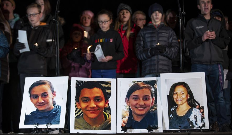 Photographs of Consuelo Alejandra Haynie, 52, right, and three of her children, 12-year-old Maylan, 14-year-old Mathew, and 15-year-old Alexis Haynie, left to right, are displayed at a candlelight vigil for the Haynie family at City Park in Grantsville, Utah, Monday, Jan. 20, 2020. Police say four members of the Haynie family were killed and one injured after being shot by a teenage family member on Jan. 17. (Spenser Heaps/The Deseret News via AP)
