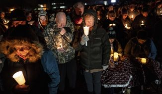 Jack and Holly Nelson, center, join others in prayer during a candlelight vigil for the Haynie family at City Park in Grantsville, Utah, Monday, Jan. 20, 2020. Police say four members of the Haynie family were killed and one injured after being shot by a teenage family member on Jan. 17. (Spenser Heaps/The Deseret News via AP)