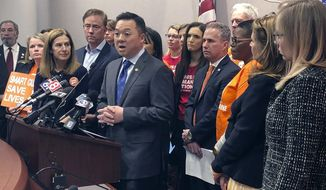 Connecticut Attorney General William Tong speaks beside Lt. Gov. Susan Bysiewicz, third from left, and Gov. Ned Lamont, fourth from left, Wednesday, Jan. 22, 2020, in Hartford, Conn., where they announced plans to join a coalition of 20 states in an upcoming lawsuit to prevent the release of 3D printed gun files on the internet. (AP Photo/Susan Haigh)